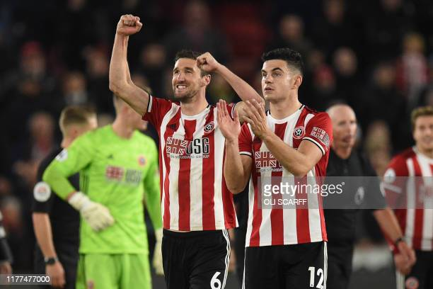 Sheffield United's English defender Chris Basham and Sheffield United's Irish defender John Egan celebrate on the pitch after the English Premier...