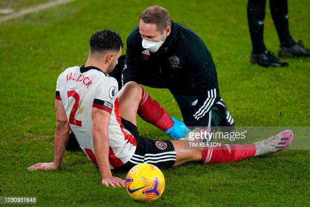 Sheffield United's English defender George Baldock receives treatment after picking up an injury during the English Premier League football match...