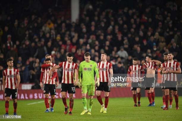 Sheffield United's English goalkeeper Dean Henderson and Sheffield United's Irish defender John Egan leave the pitch after the English Premier League...