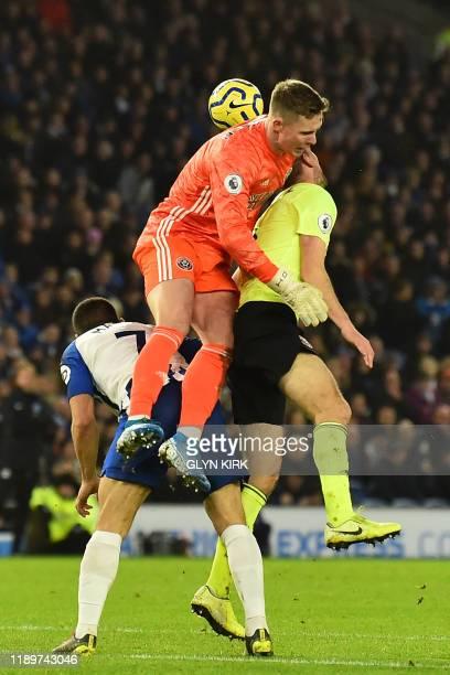 Sheffield United's English goalkeeper Dean Henderson collides with Sheffield United's English defender Chris Basham during the English Premier League...
