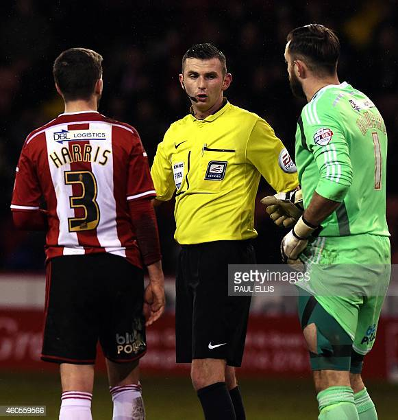 Sheffield United's English goalkeeper Mark Howard shows a rip in his shorts to referee Michael Oliver after a heavy tackle during the English League...
