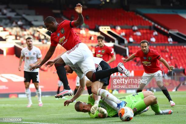 Sheffield United's English goalkeeper Simon Moore saves the ball from the feet of Manchester United's Nigerian striker Odion Ighalo during the...