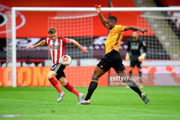 Sheffield United's English midfielder Ben Osborn vies with Wolverhampton Wanderers' French defender Willy Boly during the English Premier League...