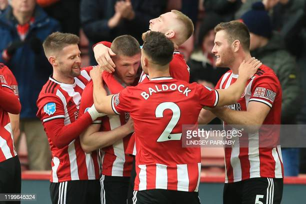 Sheffield United's English midfielder John Lundstram celebrates with teammates after scoring their second goal during the English Premier League...