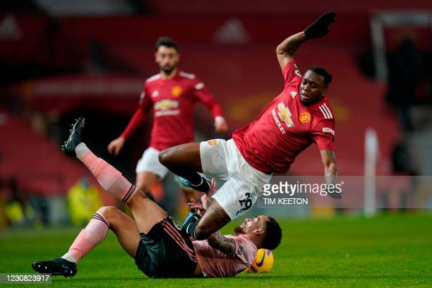 Sheffield United's English midfielder Kean Bryan tackles Manchester United's English defender Aaron Wan-Bissaka during the English Premier League...