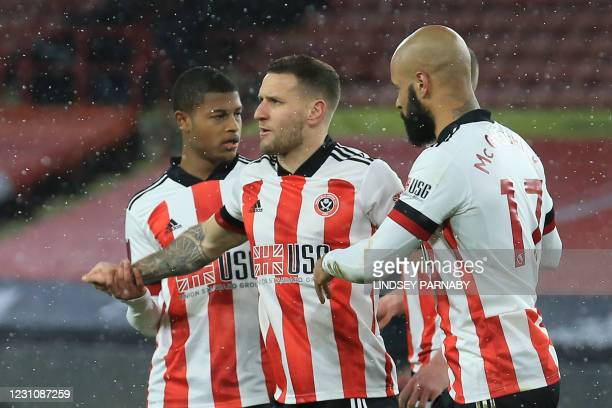 Sheffield United's English striker Billy Sharp celebrates with teammates after he takes a penalty and scores his team's first goal during the FA Cup...