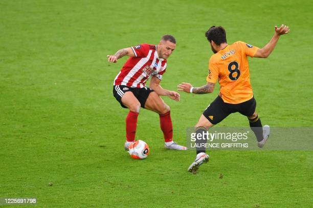 Sheffield United's English striker Billy Sharp vies with Wolverhampton Wanderers' Portuguese midfielder Ruben Neves during the English Premier League...