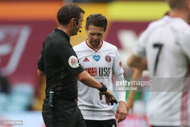 Sheffield United's English-born Northern Irish midfielder Oliver Norwood queries on the functioning of English referee Michael Oliver's watch after...