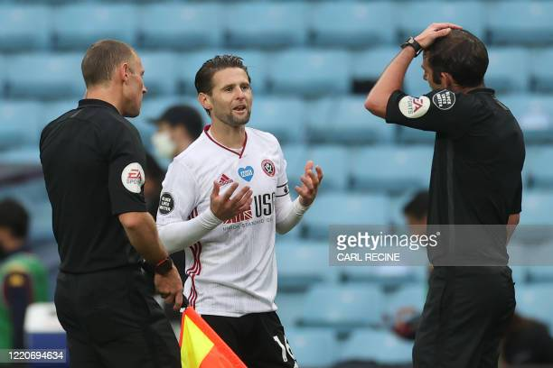 Sheffield United's English-born Northern Irish midfielder Oliver Norwood speaks with English referee Michael Oliver after the English Premier League...