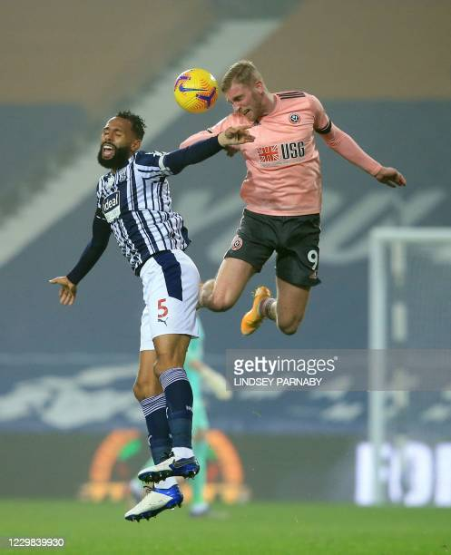 Sheffield United's Englishborn Scottish striker Oli McBurnie jumps to head the ball against West Bromwich Albion's English defender Kyle Bartley...