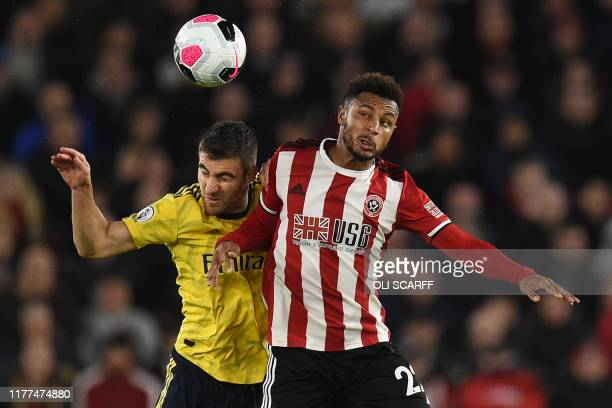 Sheffield United's French striker Lys Mousset vies with Arsenal's Greek defender Sokratis Papastathopoulos during the English Premier League football...