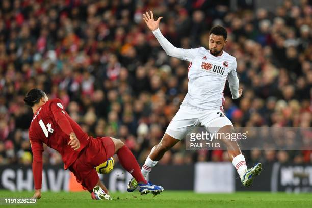 Sheffield United's French striker Lys Mousset vies with Liverpool's Dutch defender Virgil van Dijk during the English Premier League football match...