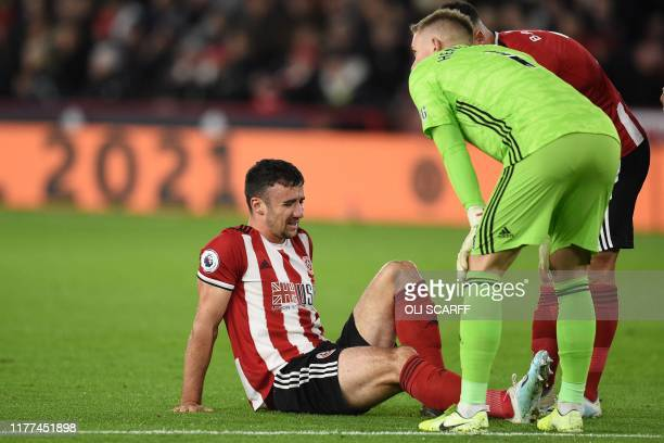 Sheffield United's Irish defender Enda Stevens picks up an injury during the English Premier League football match between Sheffield United and...