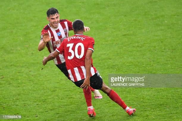 Sheffield United's Irish defender John Egan celebrates with teammate Sheffield United's Dutch striker Richairo Zivkovic after scoring a goal during...