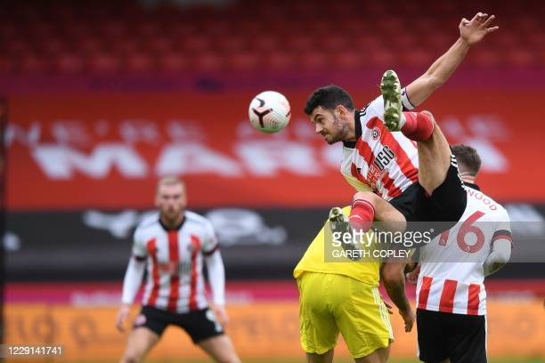 Sheffield United's Irish defender John Egan climbs onto the back of Fulham's Serbian striker Aleksandar Mitrovic to reach the ball during the English...