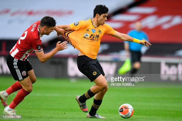 Sheffield United's Irish defender John Egan vies with Wolverhampton Wanderers' Mexican striker Raul Jimenez during the English Premier League...