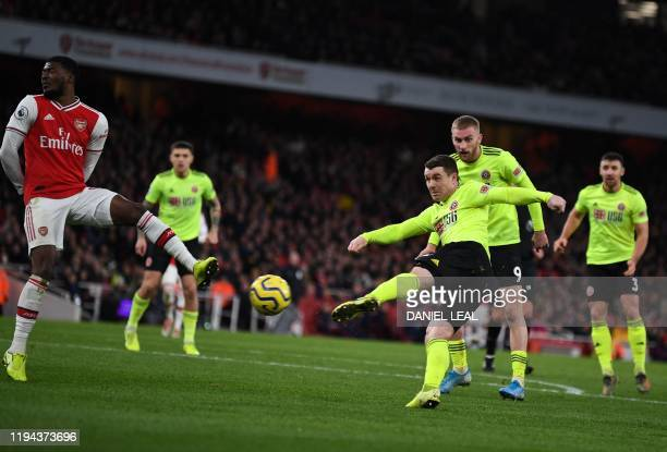TOPSHOT Sheffield United's Scottish midfielder John Fleck scores the equalising goal during the English Premier League football match between Arsenal...