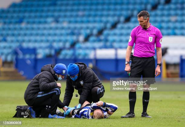 Sheffield Wednesday's Barry Bannan receives treatment as referee Andre Marriner looks on during the Sky Bet Championship match between Sheffield...