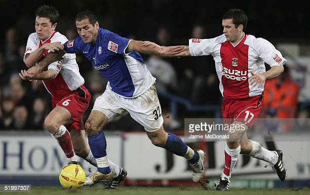 Shefki Kuqi of Ipswich slips between Stephen Hughes and Micky Doyle of Coventry during the Coca Cola Championship match between Ipswich Town and...