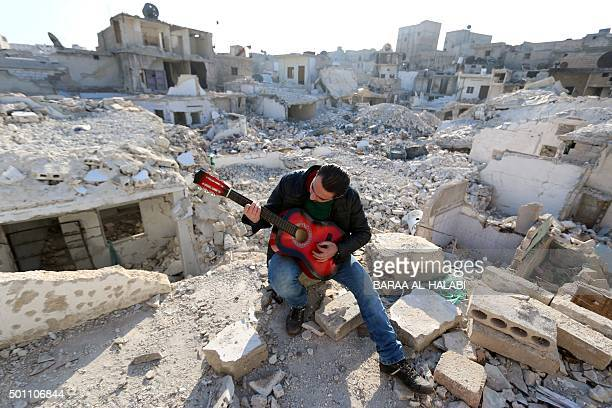 TOPSHOT Shehab a 23yearold Syrian practices the guitar amidst the rubble of buildings in the northern Syrian city of Aleppo on December 11 2015...