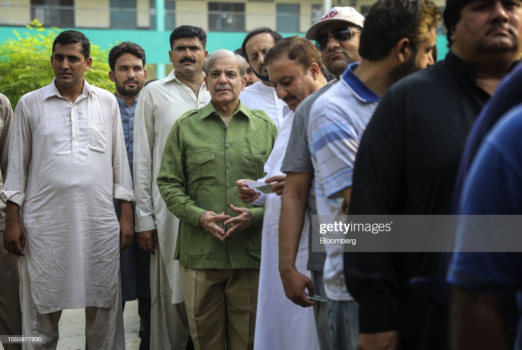 Shehbaz Sharif president of the Pakistan Muslim LeagueNawaz fourth from left waits in line to cast his vote at a polling station in Lahore Pakistan...