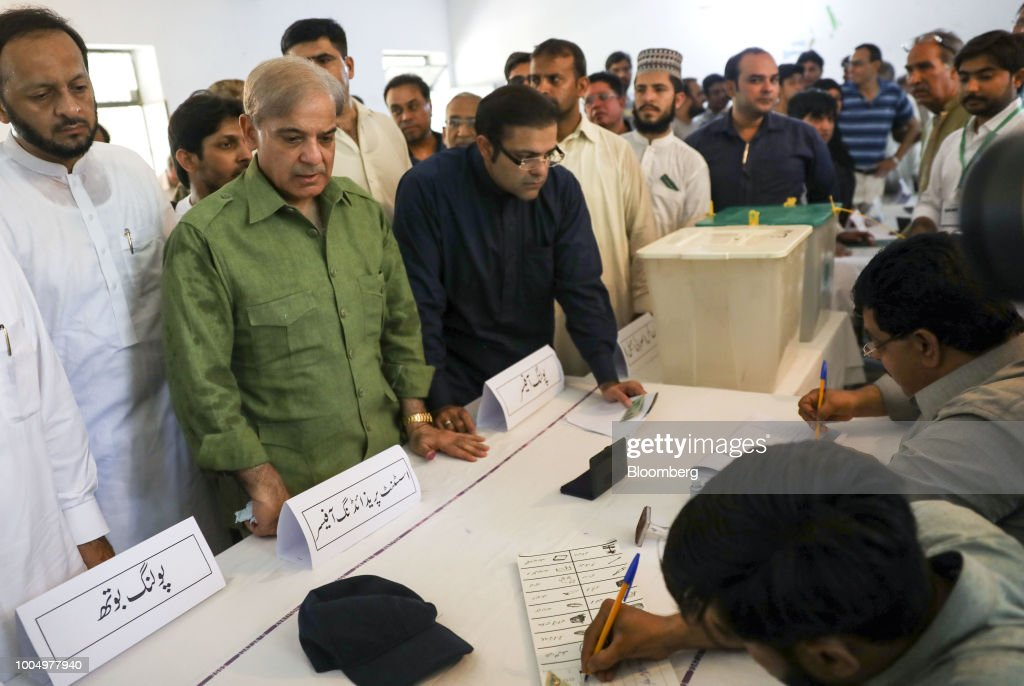 Shehbaz Sharif president of the Pakistan Muslim LeagueNawaz second from left waits to get his ballot at a polling station in Lahore Pakistan on...