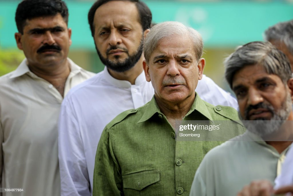 Shehbaz Sharif president of the Pakistan Muslim LeagueNawaz third from left waits in line to cast his vote at a polling station in Lahore Pakistan on.