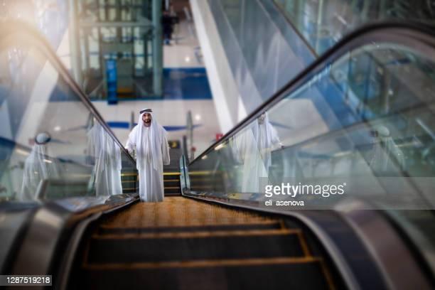 sheik in modern metro station in dubai - travolator stock pictures, royalty-free photos & images