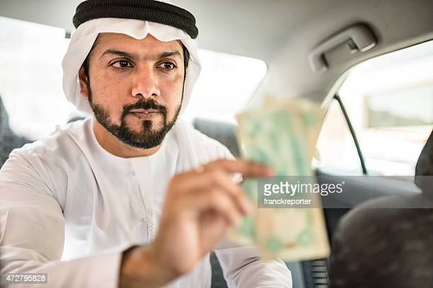 sheik inside a taxi paying the driver