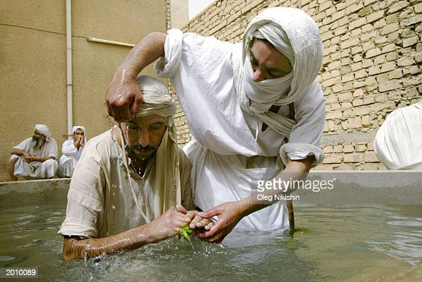 Sheik Muthana Majid a Mandaean Sabian cleric baptizes a follower May 18 2003 in Baghdad Iraq A postnuptial ceremony is performed on couples to purify...
