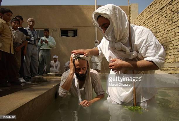 Sheik Muthana Majid a Mandaean Sabian cleric baptizes fellow Sheik Kassan Thari at a baptism ceremony May 11 2003 in Baghdad Iraq Mandaean Sabians a...