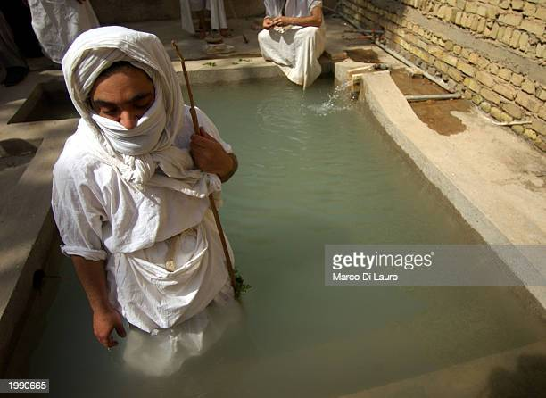 Sheik Muthana Majid a Mandaean Sabian cleric stands in a baptism pool as he begins a postnuptial baptism for an Iraqi couple May 11 2003 in Baghdad...