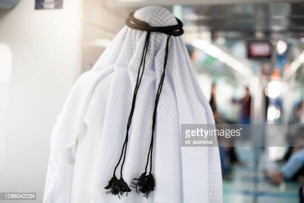 sheik riding in subway train in modern metro in dubai - human body part stock pictures, royalty-free photos & images