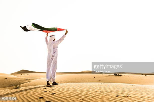 sheik waving the uae flag for national day - united arab emirates stock pictures, royalty-free photos & images