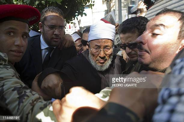 Sheik Youssef alQaradawi is protected by soldiers and people as he leaves Cairo's Tahrir Square after delivering the Friday prayer sermon on February...