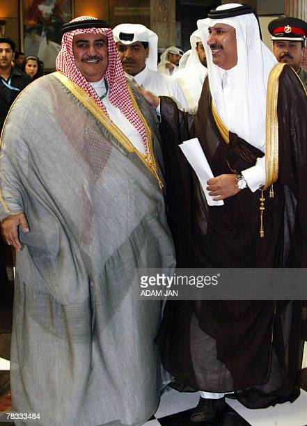 Sheikh Hamad bin Jassim bin Jaber al-Thani, Prime Minister and Foreign Minister of Qatar stands with Bahraini Foreign Minister Sheikh Khalid bin...
