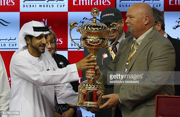 Sheikh Hamdan Bin Mohammad Bin Rashid alMaktoum crown prince of Dubai presents the owners of US horse California Chrome celebrate with the trophy...