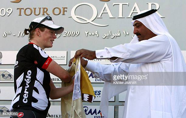 Sheikh Khaled bin Ali al-Thani, president of the Qatar Cycling Federation, gives the gold jersey to Dutch cyclist Kirsten Wild at the end of the...