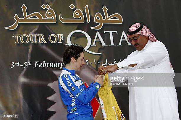 Sheikh Khaled bin Ali al-Thani, president of the Qatar Cycling Federation, gives the gold jersey to Italy's Giorgia Bronzini after she won the second...