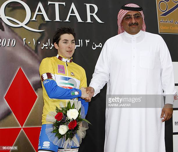 Sheikh Khaled bin Ali al-Thani, president of the Qatar Cycling Federation, shakes hands with Italy's Giorgia Bronzini after she won the second stage...