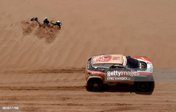 TOPSHOT Sheikh Khalid Al Qassimi of United Arab Emirates with his codriver Xavier Panseri of France steers his Peugeot during Stage 8 of the 2018...