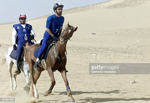 Sheikh Mohammad ibn Rashed alMaktum Dubai Crown Prince and UAE Minister of Defence rides his horse with an unidentifed participant through the...