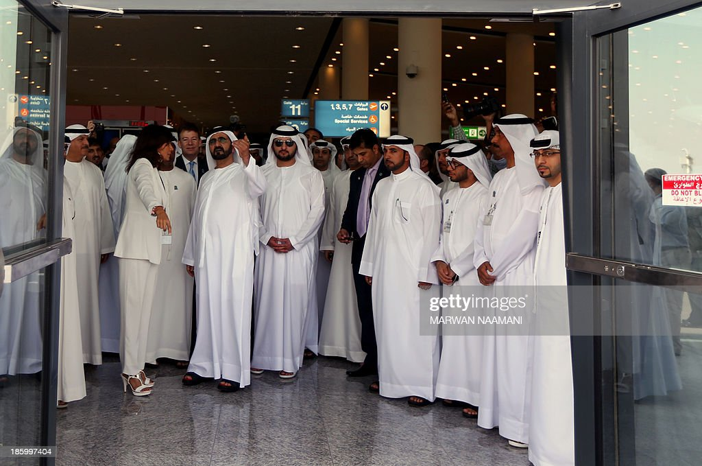 Sheikh Mohammed Bin Rashid al-Maktoum (CL) and his son Maktoum (CR) inspect the newly opened Al-Maktoum International airport, the emirate's second airport in Dubai, on October 27, 2013. The new passenger terminal opened its doors for business following an official inauguration and welcome of the first commercial flight.