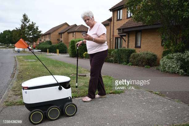 Sheila accepts a delivery through the app from an autonomous robot called Starship delivering groceries from a nearby Co-op supermarket in Milton...
