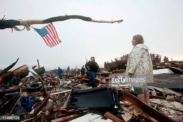 Sheila Bolte and Ashley Hailey look up at the American flag they placed in a tree branch over the remains of Ashley's home after a tornado on May 23,...