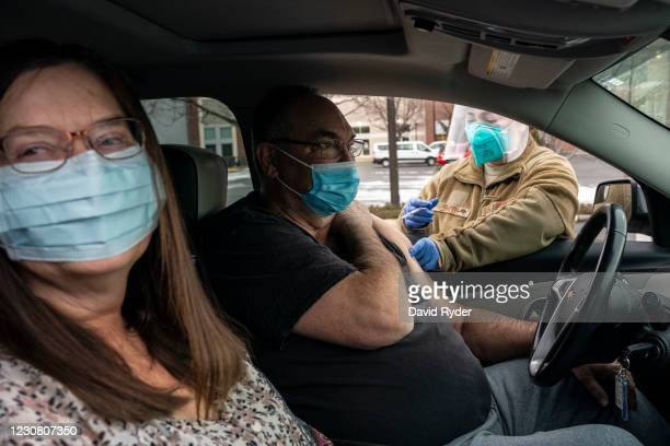 Sheila Kane and Scott Kane receive COVID-19 vaccinations from Washington National Guard medic Caitlyn Smith at Town Toyota Center on January 26, 2021...