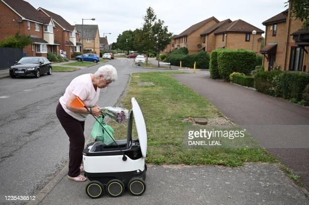Sheila picks up a delivery from an autonomous robot called Starship delivering groceries from a nearby Co-op supermarket in Milton Keynes, England on...