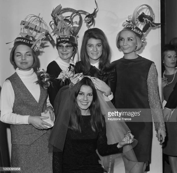 Sheila pose sur la tête de Noële Noblecourt le voile de mariée aux couleurs des 'Catherinettes' vert et jaune à Paris France le 24 novembre 1967