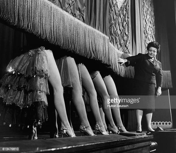 Sheila Van Damm, the owner of the Windmill Theatre, holds back the curtain as her showgirls make their final appearance. Unable to compete with the...
