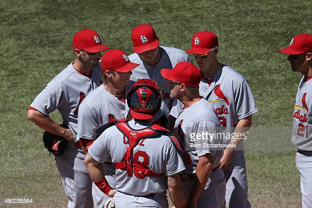 Shelby Miller of the St Louis Cardinals is visited on the mound by bullpen coach Blaise Ilsley as Tony Cruz and Matt Carpenter and Jhonny Peralta and...